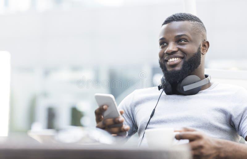 Portret uśmiechnięty amerykanin afrykańskiego pochodzenia mężczyzna używa telefon komórkowego zdjęcie royalty free