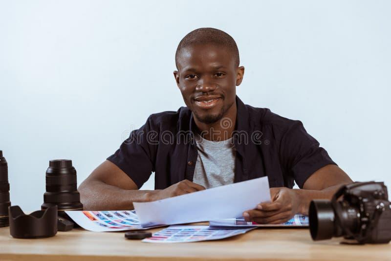 portret uśmiechnięty amerykanina afrykańskiego pochodzenia fotografa obsiadanie przy miejscem pracy z photoshoot przykładami, fot obraz royalty free