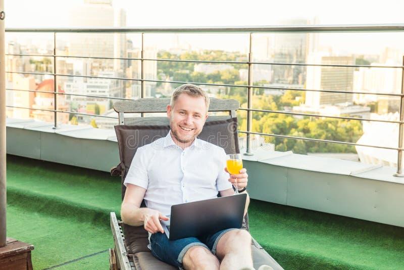 Portret uśmiechnięty biznesmen swobodnie siedzi na deckchair na biuro tarasie z Miastowym Landsca z napojem pracuje na laptopie zdjęcie stock