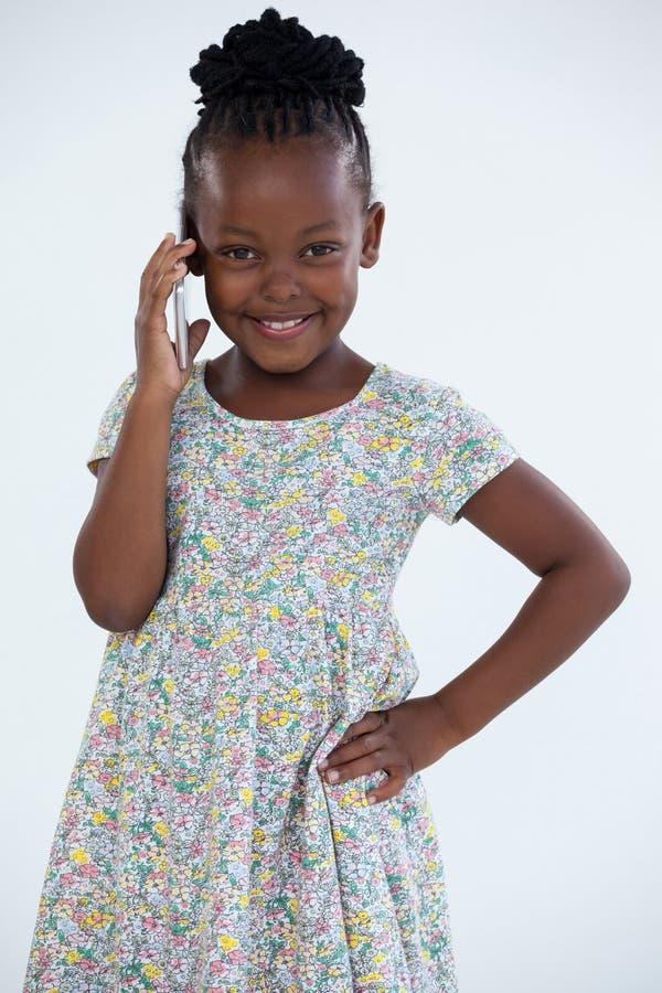 Portret uśmiechnięty bizneswoman opowiada na telefonie komórkowym z ręką na biodrze obraz stock
