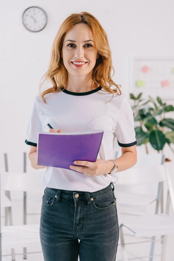 portret uśmiechnięty bizneswoman w przypadkowej odzieży z notatnikiem w rękach, biznes zdjęcia royalty free