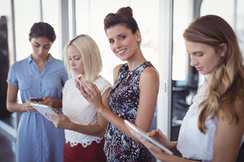 Portret uśmiechnięty bizneswoman z żeńskimi kolegami używa cyfrową pastylkę fotografia royalty free