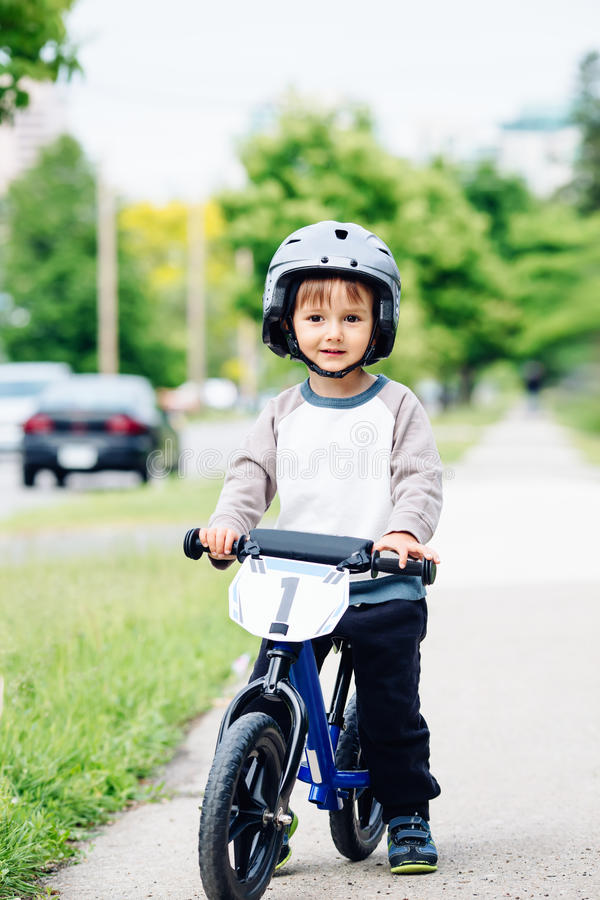 Portret uśmiechnięty chłopiec berbeć jedzie balansowego roweru bicykl w hełmie na drogowym outside outdoors na wiosna letnim dniu zdjęcia stock