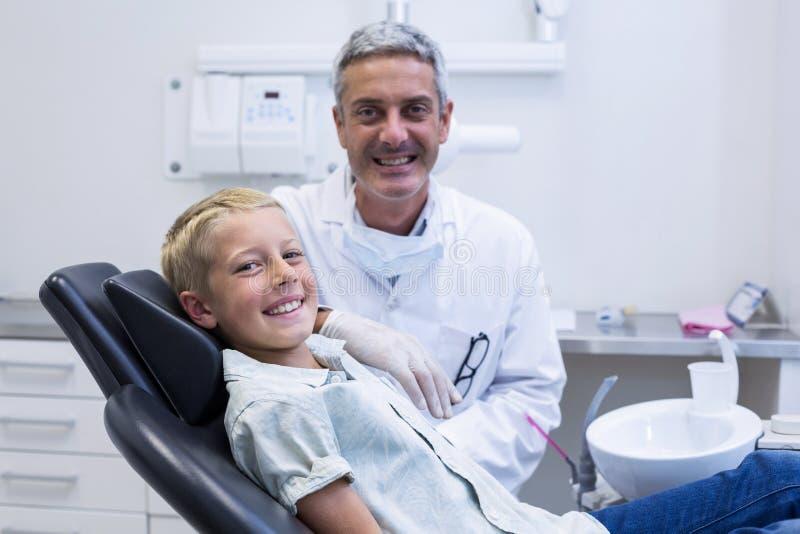 Portret uśmiechnięty dentysta i potomstwa cierpliwi obraz stock