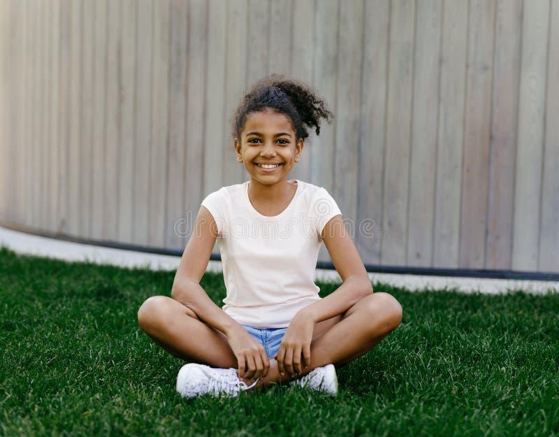 Portret uśmiechnięty dziewczyny obsiadanie na trawie zdjęcie royalty free