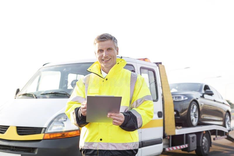 Portret uśmiechnięty holowniczy kierowca ciężarówki z schowkiem przeciw niebu fotografia stock