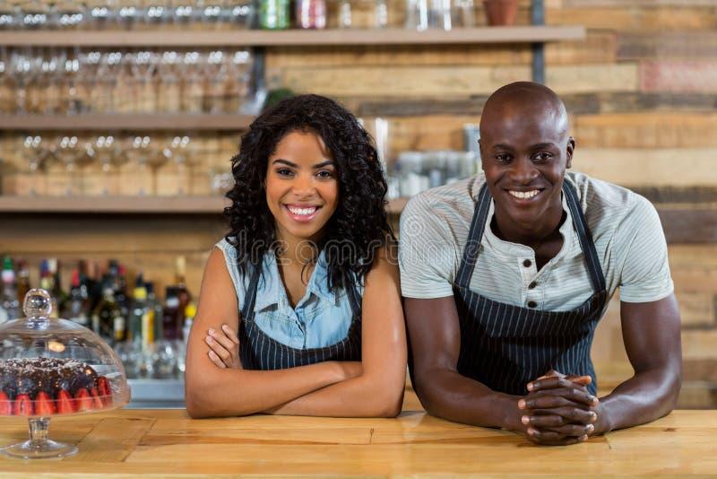 Portret uśmiechnięty kelner i kelnerka opiera przy kontuarem fotografia royalty free