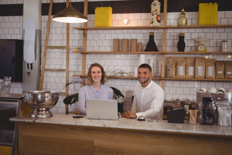 Portret uśmiechnięty kelnerki i samiec właściciel używa laptop przy kontuarem obrazy stock