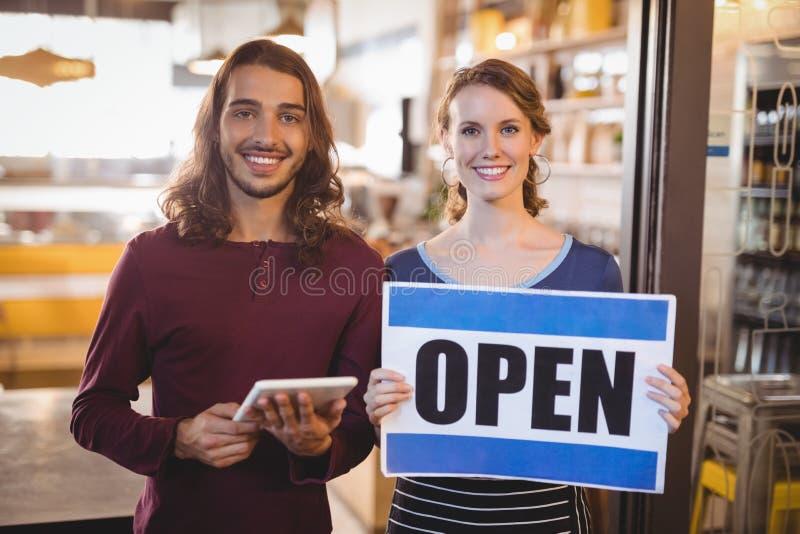 Portret uśmiechnięty kelnerki mienia plakat podczas gdy stojący mężczyzna z cyfrową pastylką obrazy stock
