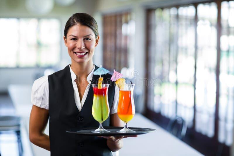 Portret uśmiechnięty kelnerki porci cocktai fotografia royalty free