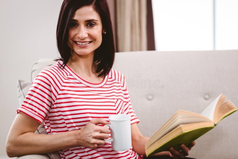 Portret uśmiechnięty kobiety mienia książkowy i kawowy kubek obrazy stock