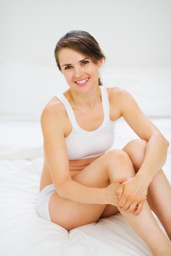 Portret uśmiechnięty kobiety obsiadanie na łóżku zdjęcia royalty free
