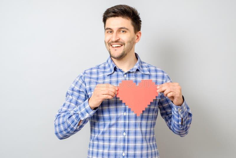 Portret uśmiechnięty mężczyzna mienia czerwieni papieru piksla serce zdjęcie stock
