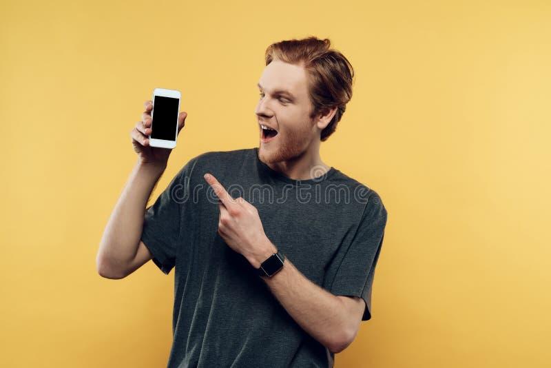 Portret uśmiechnięty mężczyzna mienia smartphone zdjęcie royalty free