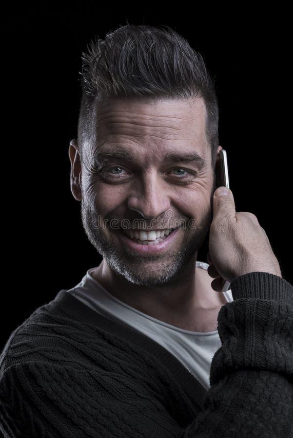 Portret uśmiechnięty mężczyzna patrzeje kamerę opowiada na telefonie komórkowym Odizolowywaj?cy na czarny tle zdjęcia royalty free