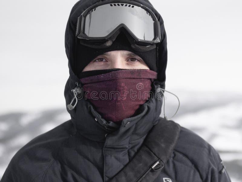 Portret uśmiechnięty mężczyzna w błękitnych narciarstw szkłach przeciw głębokim pięknym lasów spojrzeniom przy kamerą zdjęcia stock
