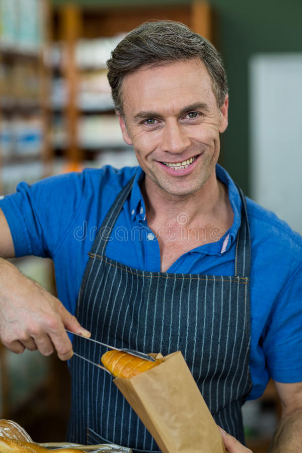 Portret uśmiechnięty męskiego personelu kocowania chleb w papierowej torbie zdjęcie royalty free