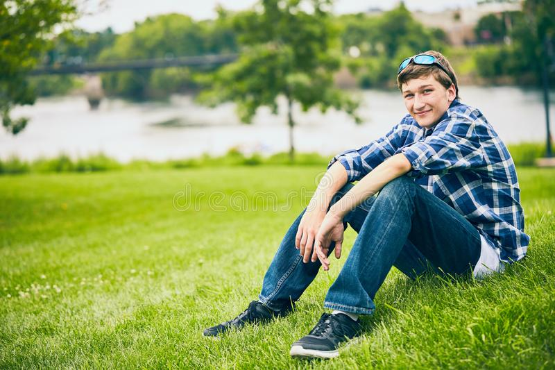 Portret uśmiechnięty młodego człowieka obsiadanie na trawie fotografia stock