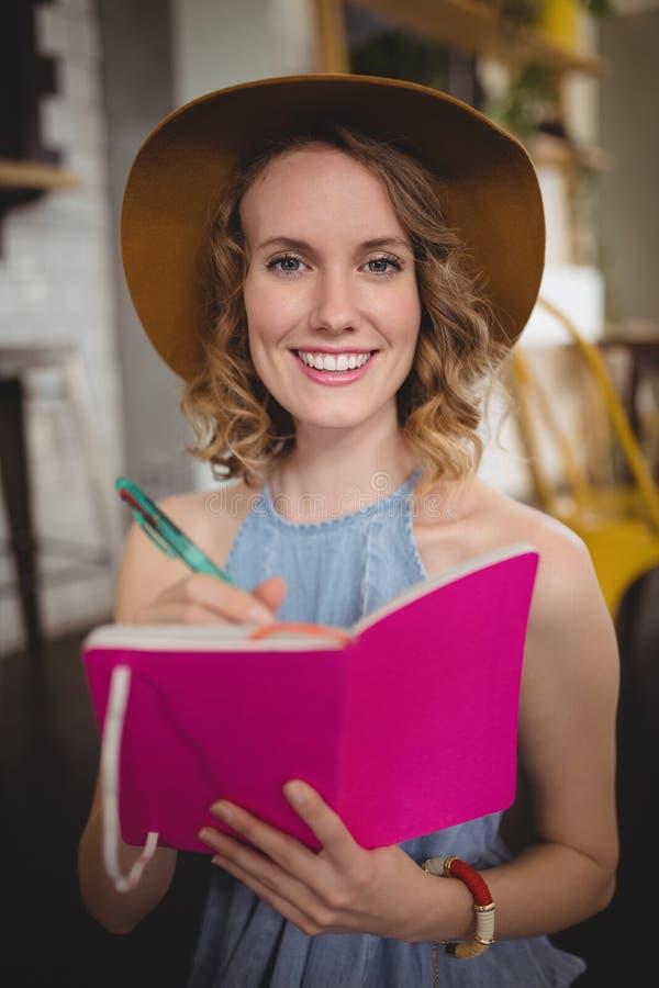 Portret uśmiechnięty młodej kobiety mienia menchii nabiał z piórem fotografia stock