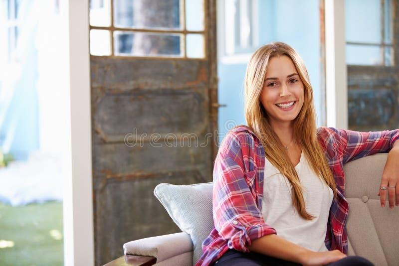 Portret Uśmiechnięty młodej kobiety obsiadanie Na kanapie W Domu obrazy royalty free