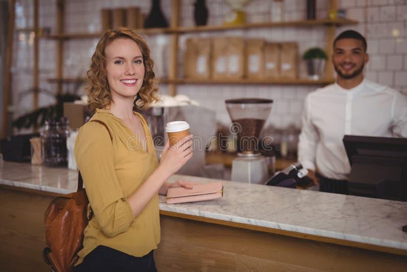 Portret uśmiechnięty młody żeński klient trzyma rozporządzalną filiżankę przy kontuarem przeciw kelnerowi obraz royalty free
