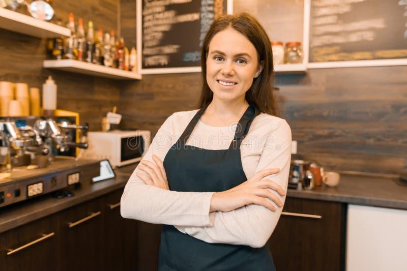 Portret uśmiechnięty młody żeński sklepu z kawą właściciel, ufna kobieta z rękami krzyżował pozycję przy kontuarem zdjęcia stock