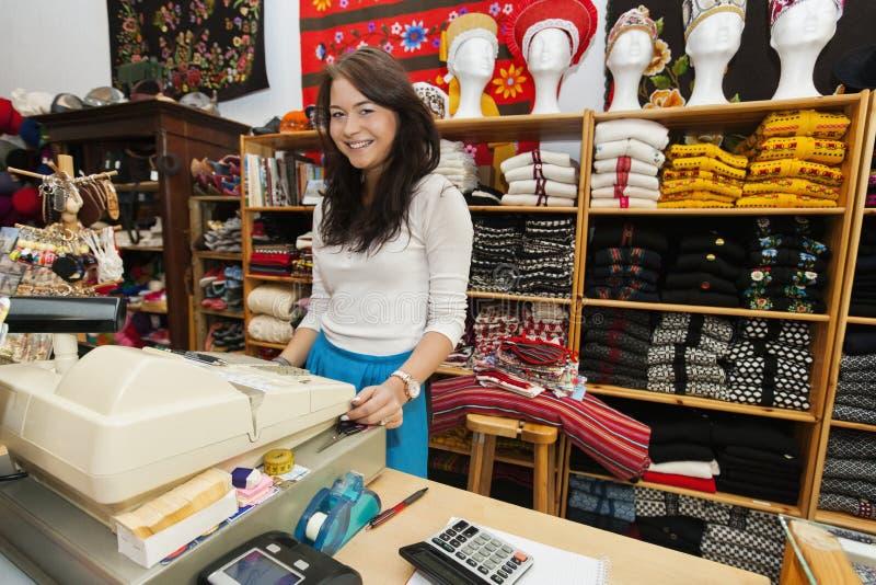 Portret uśmiechnięty młody żeński sprzedawca przy kasa stojakiem w prezenta sklepie fotografia stock