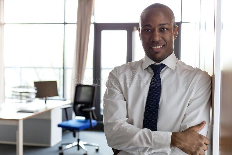 Portret uśmiechnięty młody biznesmen z rękami krzyżował opierać na spiżarni w biurze fotografia royalty free