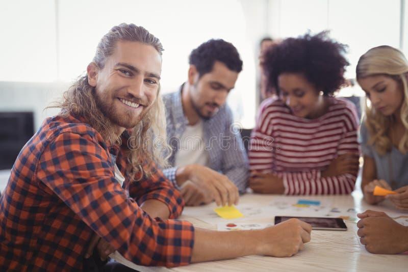Portret uśmiechnięty młody biznesmena obsiadanie z kolegami przy biurkiem zdjęcie stock