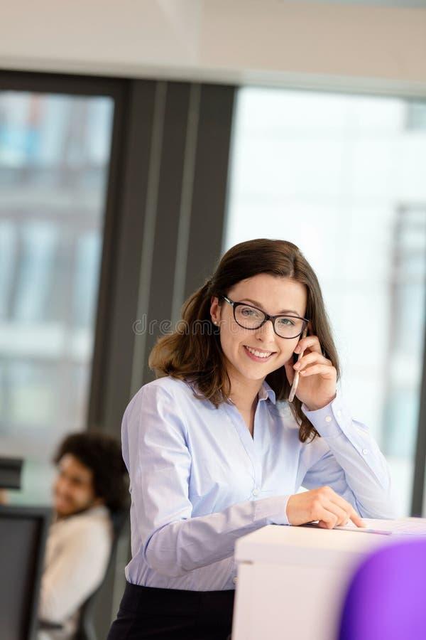 Portret uśmiechnięty młody bizneswoman opowiada na telefonie komórkowym przy biurem zdjęcie stock