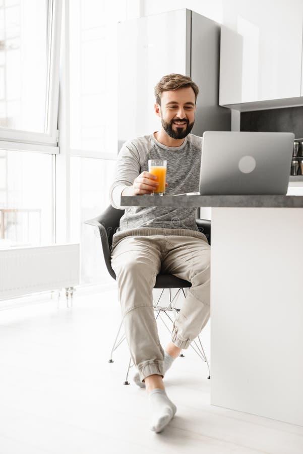 Portret uśmiechnięty młody człowiek pije sok pomarańczowego obrazy royalty free
