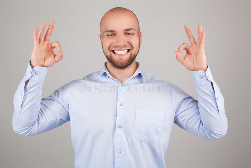 Portret uśmiechnięty młody człowiek w białej koszula pokazuje ok gest i patrzeje kamerę nad bielem podczas gdy trwanie zdjęcie royalty free