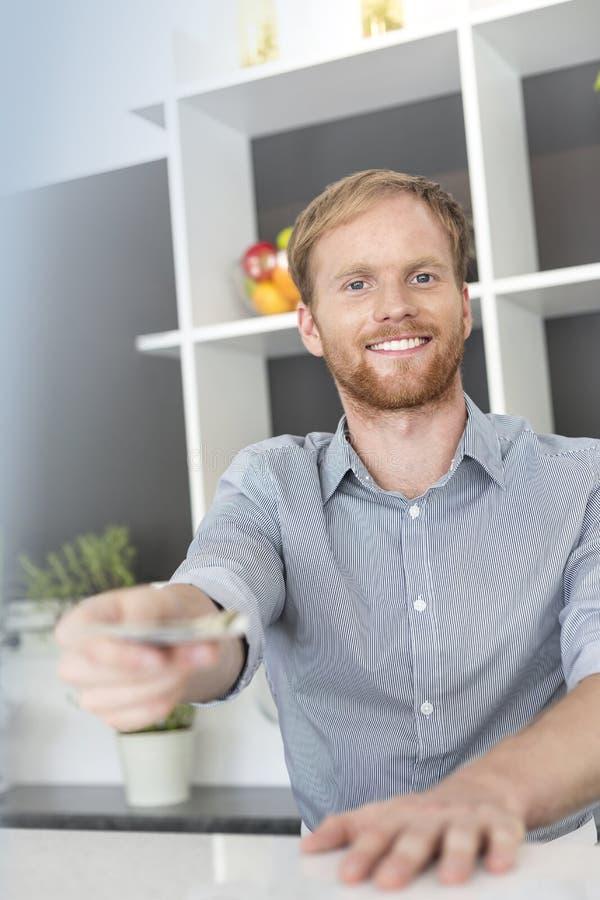 Portret uśmiechnięty młody kelner daje pieniądze podczas gdy stojący przy kontuarem w restauracji obrazy stock