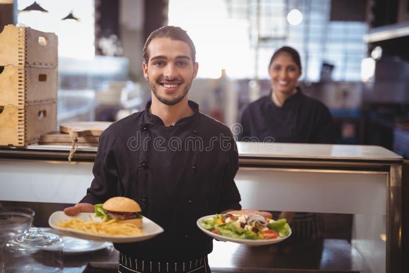 Portret uśmiechnięty młody kelner porci jedzenie podczas gdy stojący przeciw kelnerce fotografia stock