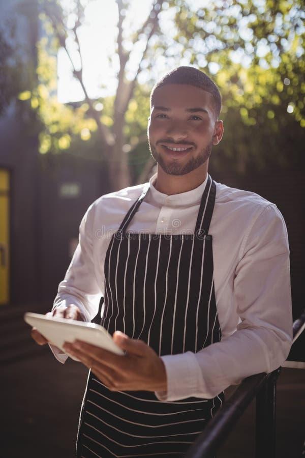 Portret uśmiechnięty młody kelner używa cyfrową pastylkę podczas gdy opierający na ostro protestować fotografia royalty free