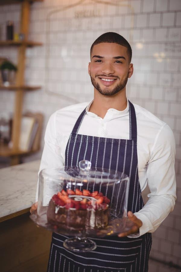 Portret uśmiechnięty młody kelnera mienia tort na szklanym cakestand zdjęcia stock