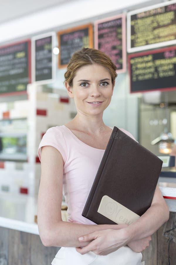 Portret uśmiechnięty młody kelnerki mienia menu podczas gdy stojący przeciw kontuarowi przy restauracją obraz royalty free