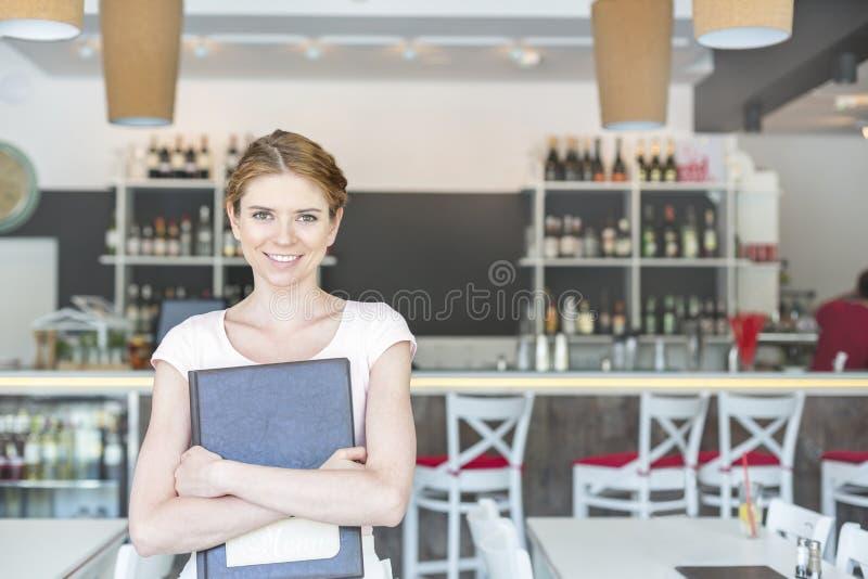 Portret uśmiechnięty młody kelnerki mienia menu podczas gdy stojący przy restauracją fotografia stock