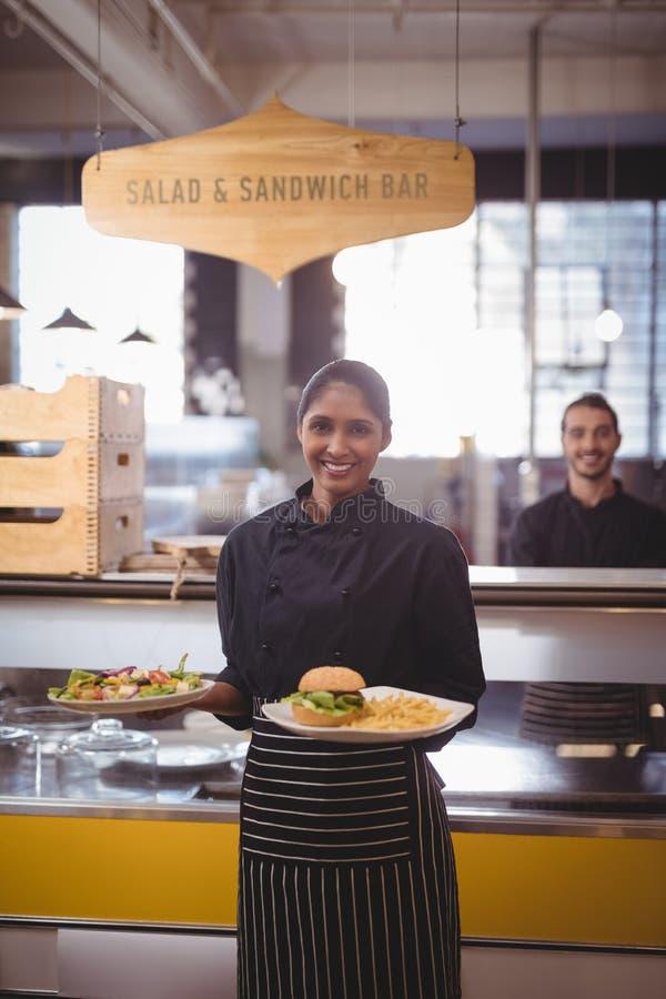 Portret uśmiechnięty młody kelnerki porci jedzenie podczas gdy stojący przeciw kelnerowi obraz royalty free