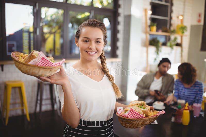 Portret uśmiechnięty młody kelnerki przewożenia jedzenie w łozinowych koszach fotografia stock