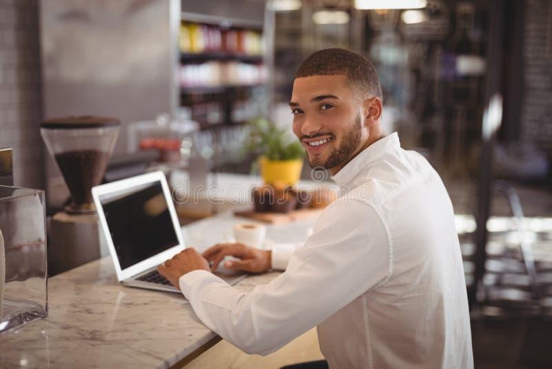 Portret uśmiechnięty młody męski właściciela obsiadanie z laptopem przy kontuarem obraz royalty free