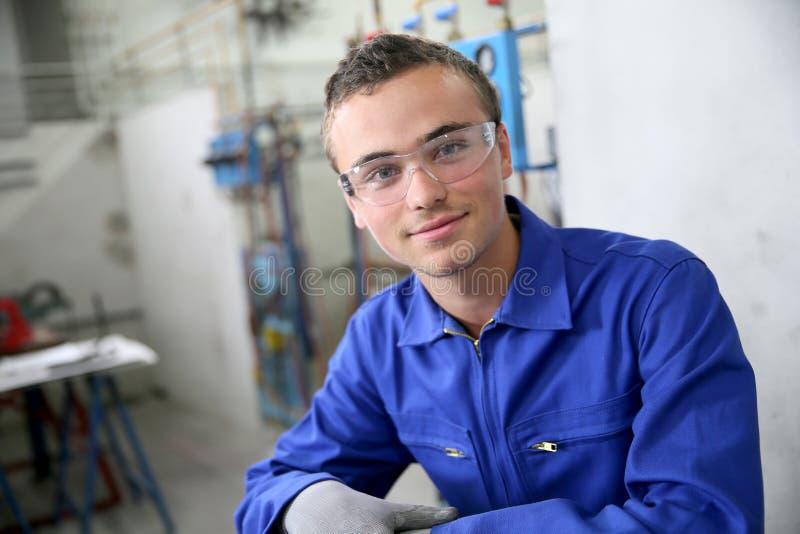 Portret uśmiechnięty młody praktykant w plumbery zdjęcia stock