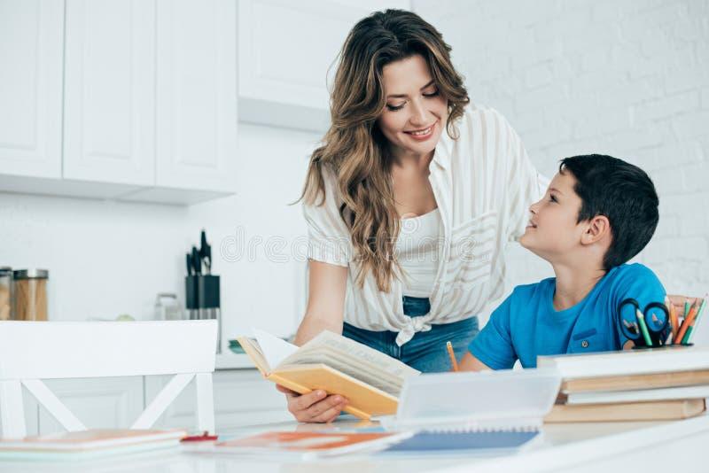 portret uśmiechnięty macierzysty pomaga syn z pracą domową w kuchni obraz royalty free