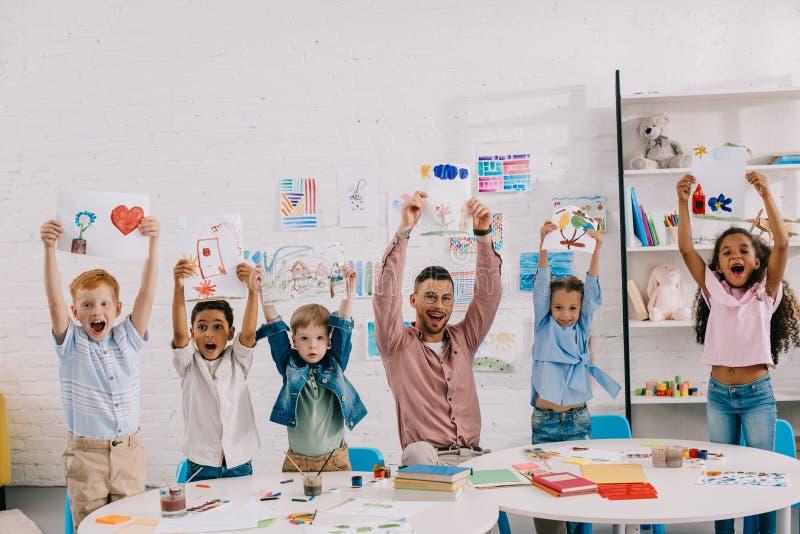 portret uśmiechnięty nauczyciel i wieloetniczni dzieciaki pokazuje obrazki w rękach fotografia stock