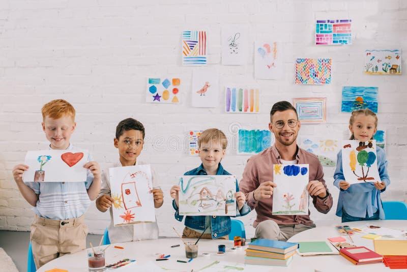 portret uśmiechnięty nauczyciel i wielokulturowi preschoolers pokazuje kolorowych obrazki w rękach zdjęcia royalty free