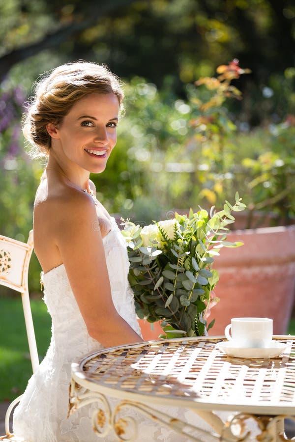 Portret uśmiechnięty panny młodej mienia bukiet podczas gdy siedzący na krześle obrazy stock