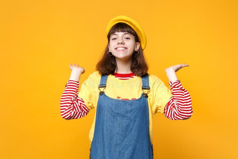 Portret uśmiechnięty powabny dziewczyna nastolatek w francuskim berecie, drelichowi sundress rozprzestrzenia ręki odizolowywać na fotografia royalty free