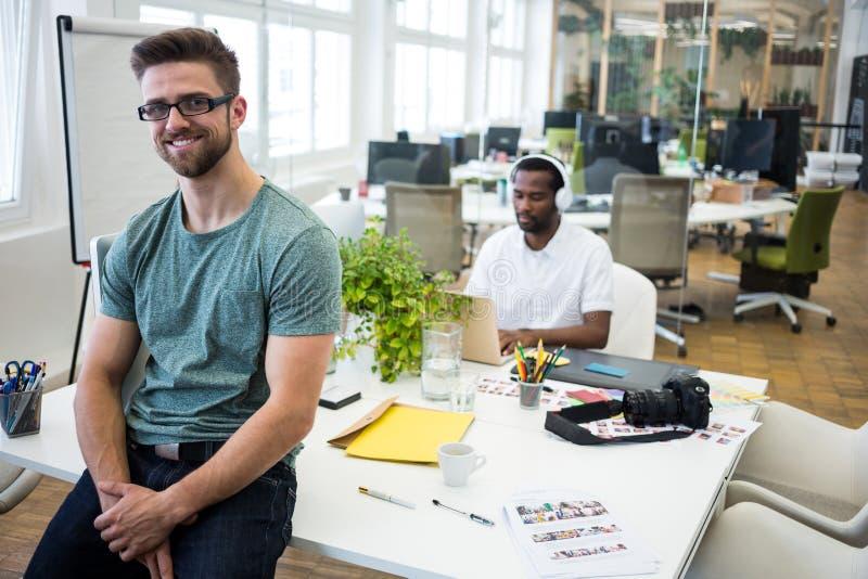 Portret uśmiechnięty projektant grafik komputerowych obsiadanie na jego biurku zdjęcie stock