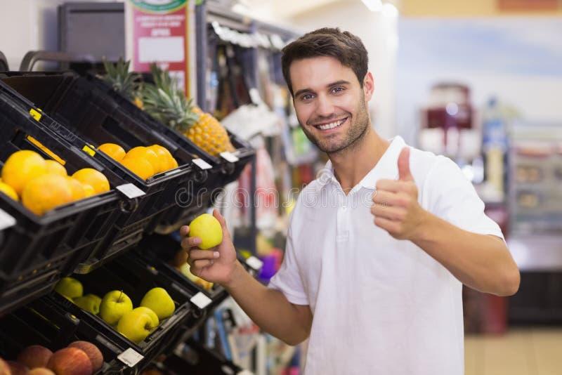 Portret uśmiechnięty przystojny mężczyzna kupuje owoc z kciukiem up zdjęcia stock