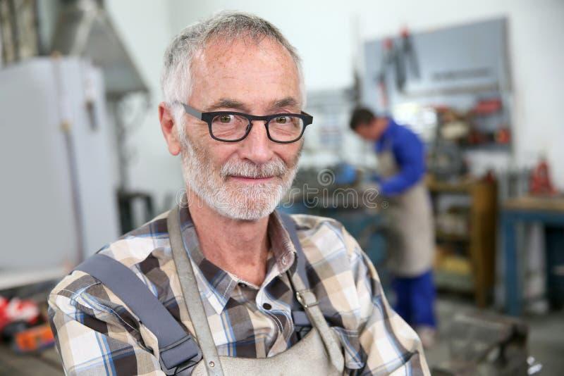 Portret uśmiechnięty starszy ślusarz w warsztacie zdjęcia stock